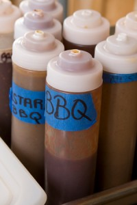 Bottles of BBQ sauce sit waiting to top off a great slider