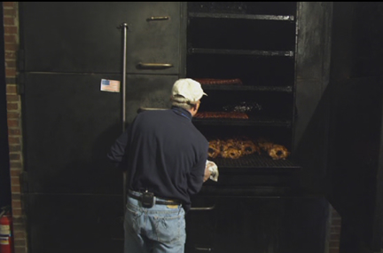 Starr Teel pulling smoked chicken from smoker