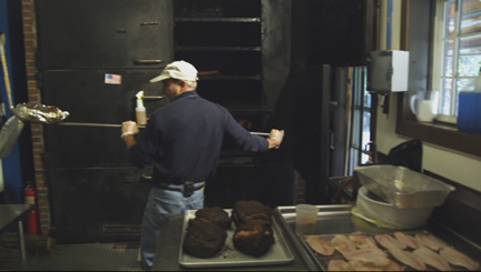 Starr Teel removing ribs from smoker at Hubba Hubba Smokehouse